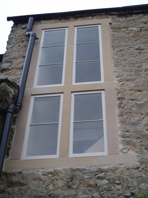 The new stonework complete. The new wooden window frames add the finishing touch.